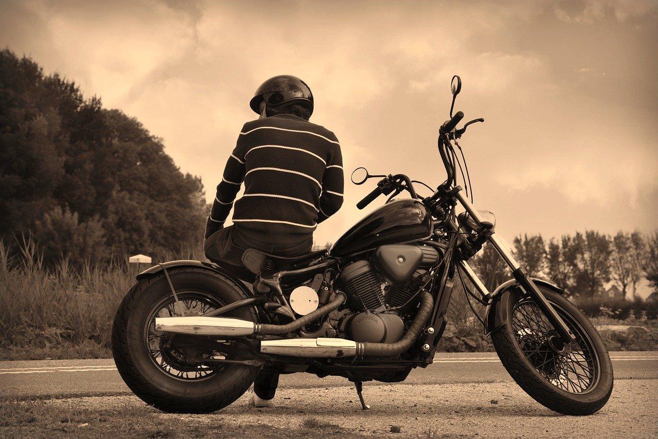 man sitting sideways on motorcycle by road