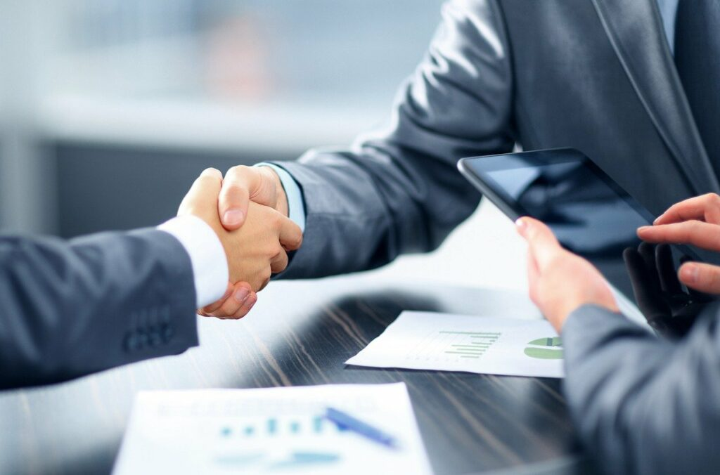 Two people shaking hands at the end of a deal