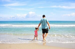 A father walking with his daughter on the beach.