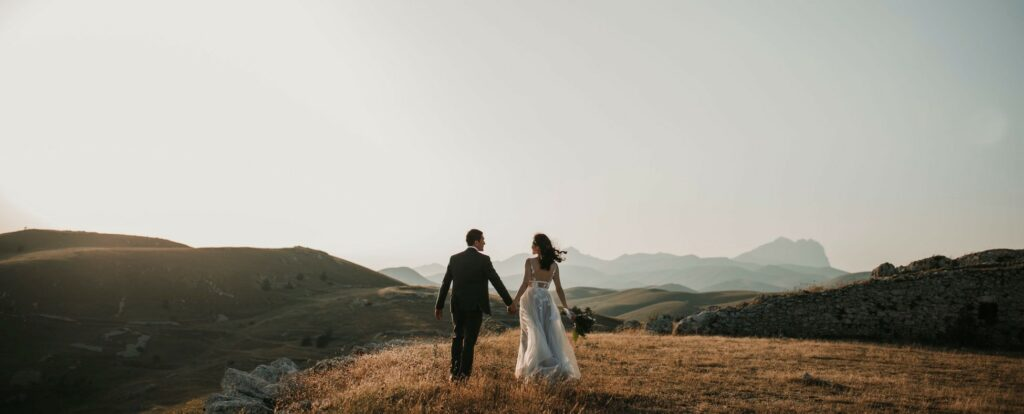 A bride and groom holding hands overlooking a scenic pasture